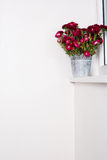 Red flowers in metal vase Stock Images