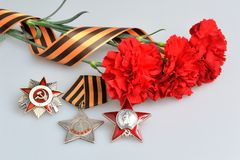 Red flowers tied with Saint George ribbon, orders of Great Patriotic War Stock Image