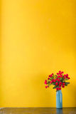 Red flowers in vase on yellow background Stock Images