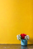 Red flowers in vase on yellow background Stock Photos
