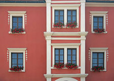 Red flowers in window. Boxes beneath white windows on the front of a house Stock Photo
