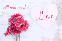 Red flowers with wooden heart and words All You Need Is Love Royalty Free Stock Photography