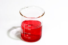 Red fluid. Graduated beaker with red fluid on bright background Stock Photo