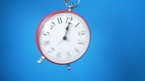 Red flying alarm clock on blue background.