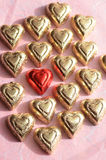 Red foil wrapped heart shape chocolate piece amid gold. Red foil wrapped heart shape chocolate candy piece amid rows of gold foil wrapped chocolate hearts  for Stock Images