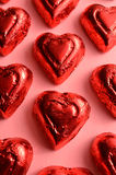 Red foil wrapped heart shape chocolate piece. Close up of red foil wrapped heart shape chocolate candy pieces on pink paper for celebrations and holidays such as Royalty Free Stock Photos