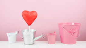 The red foiled chocolate heart stick with small silver watering can and small pink bucket Stock Photos
