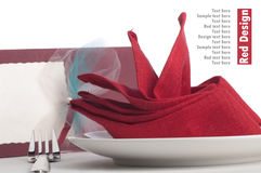 Red folded napkin. On plate for table set isolated on white background royalty free stock photography