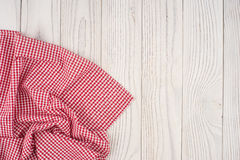 Red folded tablecloth over bleached wooden table. Top view Stock Photos