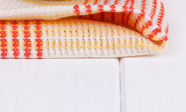 Red folded tablecloth over wooden table. Red folded tablecloth over white wooden table Stock Photo