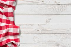 Table with red picnic cloth top view background. Red folded tablecloth with white wooden table Stock Photography
