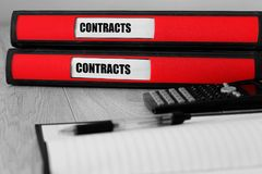 Red folders with contracts written on the label on a desk Royalty Free Stock Images