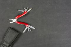 Red folding multifunctional tool for anglers. Royalty Free Stock Images