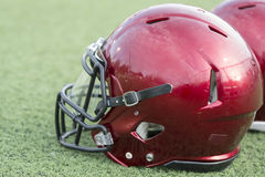 Red football helmets on artificial turf Royalty Free Stock Images