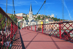 Red footbridge on Saone river and church Royalty Free Stock Images