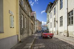 A red Ford Mustang convertible drives by a narrow cobbled street in Tallinn. Tallin is the capital and largest city of Estonia. Tallinn`s Old Town is one of the royalty free stock photo