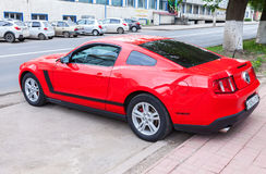 Red Ford Mustang parked up at the city street in summer day Stock Photos