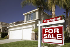 Red Foreclosure For Sale Real Estate Sign and Hous Royalty Free Stock Images