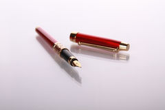 Red fountain-pen on mirror table Royalty Free Stock Photos