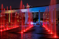 Red Fountains. Red-illuminated fountains at Marina Barrage, Singapore. Parts of the Flyer observatory wheel and the skyline are visible in the background. Long Royalty Free Stock Image