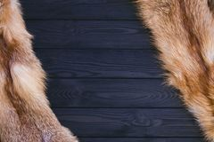 Red fox skin on a black wooden background. Beautiful fur of a red fox.  Stock Photography
