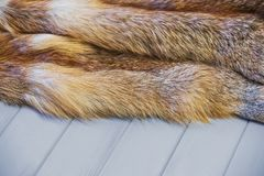 Red fox skin on a gray wooden background. Beautiful fur of a red fox.  Royalty Free Stock Images