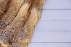 Red fox skin on a gray wooden background. Beautiful fur of a red fox.  Royalty Free Stock Photos