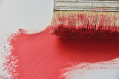 Red. Fragment of a brush with a red paint on a light background Royalty Free Stock Image