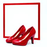 Red frame with high heels. In front of white background royalty free stock photography