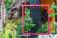 Red frame hung on tree in lush garden setting Royalty Free Stock Photo