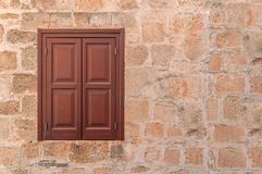 Red frame of one modern wooden window on on left side on yellow wall stock images