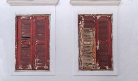 Red frame of two old rusty wooden window on gray aged home house stock photography