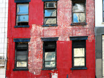Red frame windows. The decayed facade of an aging building in lower Manhattan, New York City Stock Photo