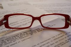 Red Framed Eyeglass on Top of Paper Royalty Free Stock Photography