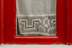 Red framed window with lace curtain Royalty Free Stock Photo