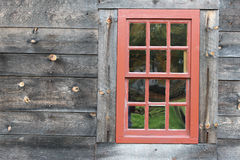 Red framed window. On a weathered board sided home Stock Image