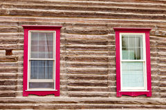 Red framed windows in log house wall architecture Stock Photography