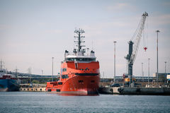 Red freight ship in front of port facilities and cranes Stock Image