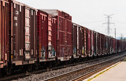 Red freight train box cars in perspective Royalty Free Stock Image