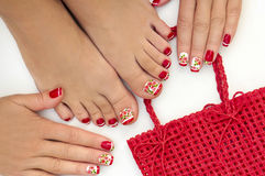 Red French manicure and pedicure. Red French manicure and pedicure with design of roses on a white background stock photos