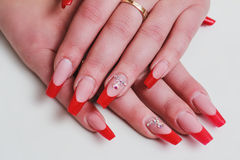 Red french nail art with rhinestones Stock Images
