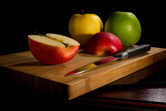 Red fresh apples, chopped up on the old board. On a wooden table. Top view royalty free stock photography