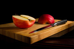 Red fresh apples, chopped up on the old board. On a wooden table. Top view stock photo