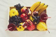 Red fresh juice with apples, pears, bananas, grapes and pomegranate fruits in white wooden tray on bed sheet. Top view.  Healthy l Stock Photography
