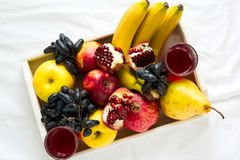 Red fresh juice with apples, pears, bananas, grapes and pomegranate fruits in white wooden tray on bed sheet. Top view.  Healthy l Royalty Free Stock Image
