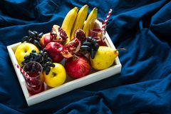 Red fresh juice with apples, pears, bananas, grapes and pomegranate fruits in white wooden tray on blue bed shee Royalty Free Stock Images