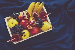 Red fresh juice with apples, pears, bananas, grapes and pomegranate fruits in white wooden tray on blue bed shee Stock Photos