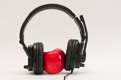 Red, fresh, juicy apple with black headphone. stock photos
