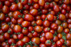 A group of fresh tiny tomatoes. Red fresh and little tomatoes with green leaves at the market bench Stock Photography
