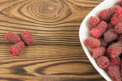 Red fresh raspberries in bowl on old wooden background stock photography